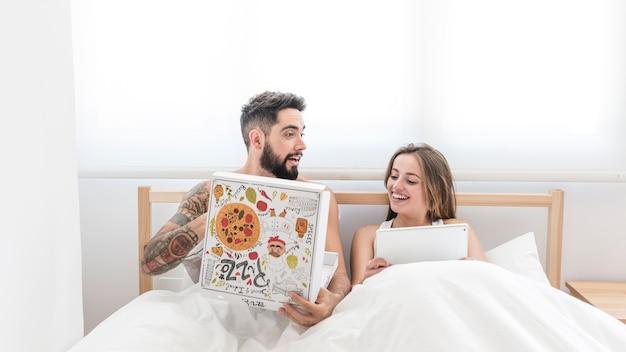 Homem comendo pizza enquanto sua esposa usando tablet digital