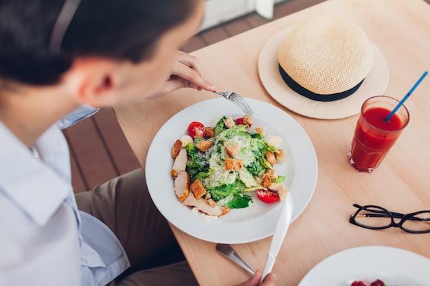 Homem comendo salada caesar e bebendo suco de tomate no restaurante. viajante almoçando no café.