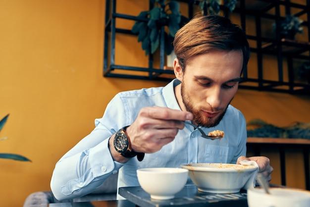 Homem comendo sopa de lanche em um restaurante