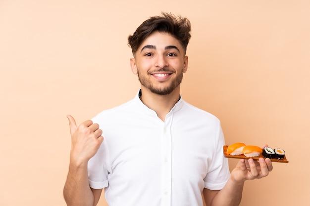 Homem comendo sushi isolado em bege apontando para o lado