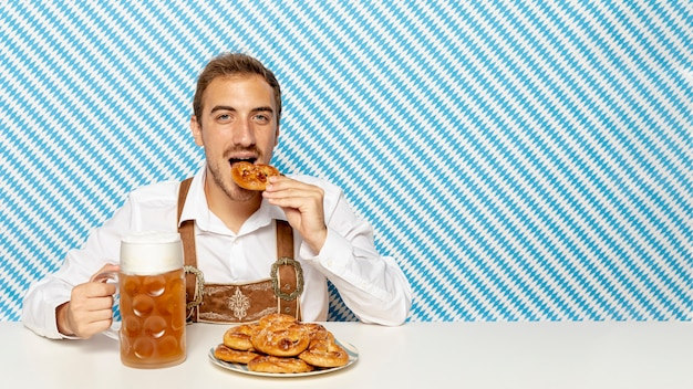 Homem, comer, alemão, pretzels, com, espaço cópia