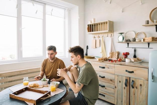 Homem, comer, café manhã, com, seu, amigo, usando, cellphone, em, cozinha