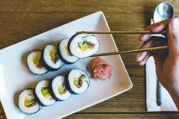 Homem, comer, tradicional, coreano, gimbap, arroz, rolos, com, chopsticks