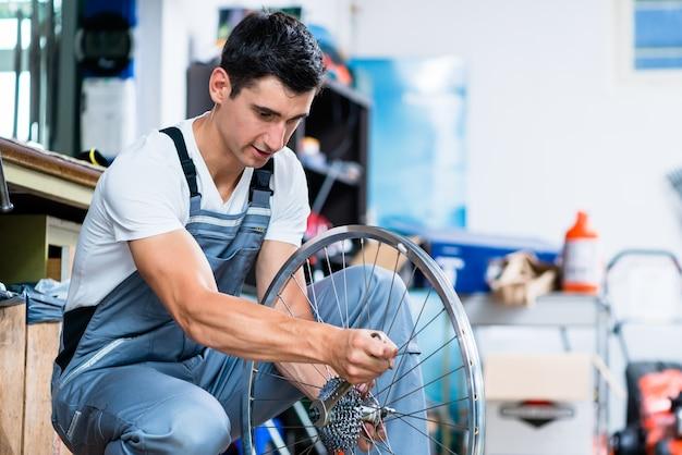 Homem como mecânico de bicicletas trabalhando em oficina