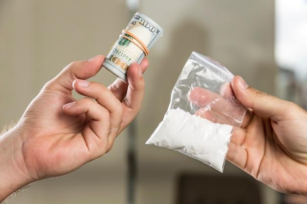 Homem comprando cocaína com um rolo de dólares