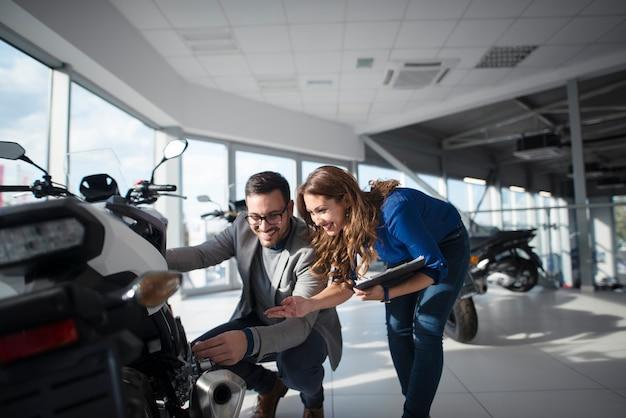Homem comprando motocicleta veloz com ajuda de linda vendedora morena