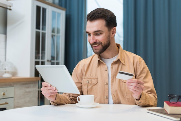 Homem compras on-line usando tablet e cartão de crédito