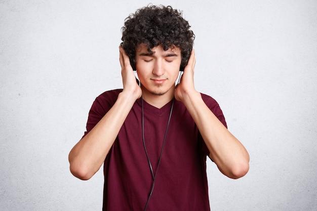 Homem concentrado, com cabelos crespos, usa fones de ouvido e ouve música com prazer, mantém os olhos fechados, veste camiseta casual