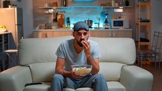 Homem concentrado com máscara de dormir sentado em frente à televisão