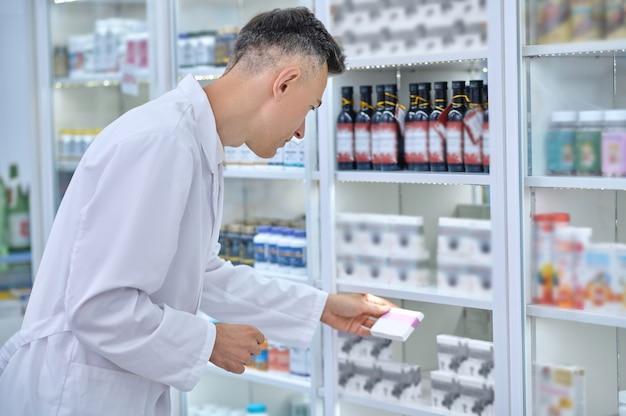 Homem concentrado de jaleco revisando medicamentos na farmácia