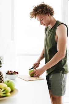 Homem concentrado em pé na cozinha e cozinhar