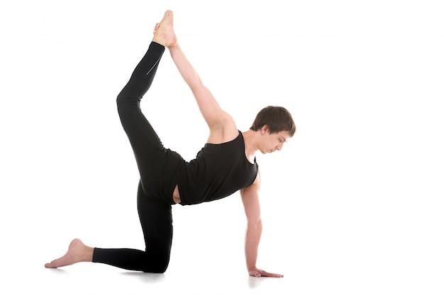 Homem concentrado em uma postura de yoga