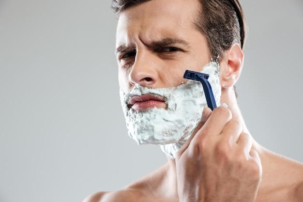 Homem concentrado faz a barba