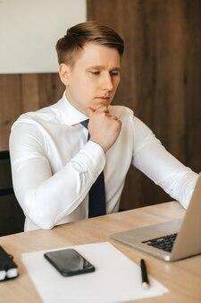 Homem concentrado na camisa branca, trabalhando com o laptop no escritório.