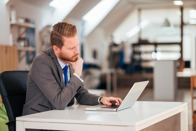 Homem concentrado seguro novo que senta-se no escritório pela tabela que trabalha com portátil e que usa o teclado.