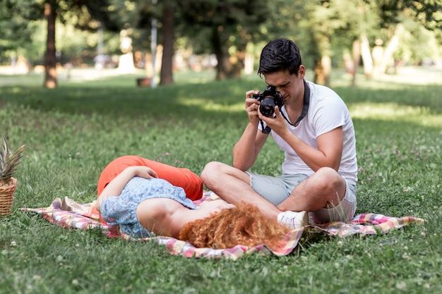 Homem concentrado, tirando fotos de sua namorada