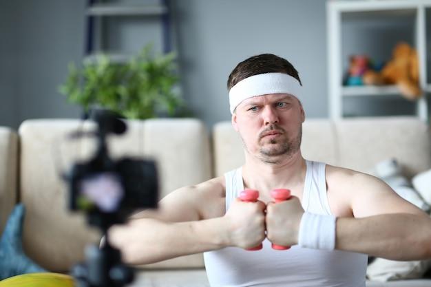 Homem concentrado usando halteres para fazer exercício