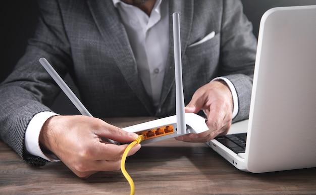 Homem conectando o cabo de internet ao roteador wi-fi.