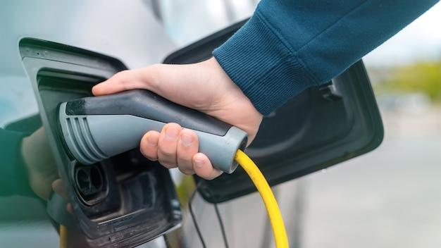 Homem conectando o carregador a um carro elétrico na estação de carga