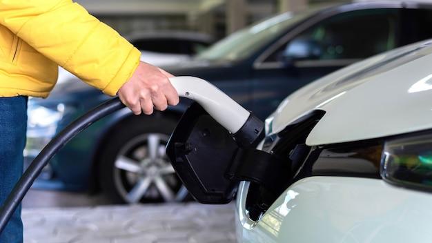 Homem conectando o carregador em um carro elétrico branco