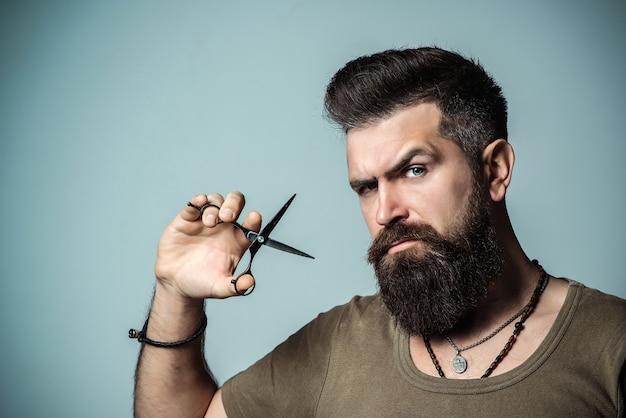 Homem confiante barbeiro profissional com uma tesoura. cabeleireiro elegante na barbearia. publicidade e barbearia conceito
