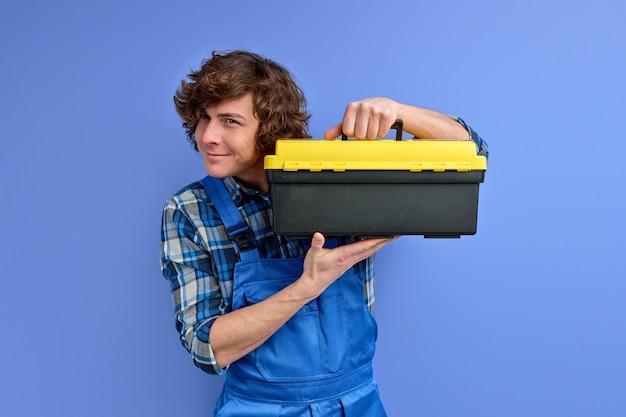Homem confiante com caixa de ferramentas para conserto isolada em fundo roxo