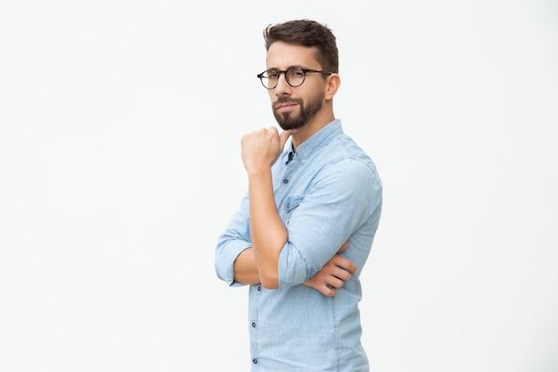 Homem confiante com mão no queixo, olhando para a câmera
