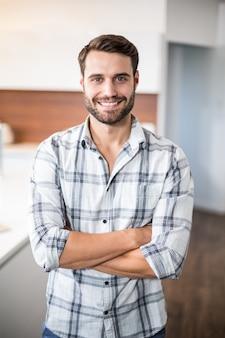 Homem confiante com os braços cruzados pelo balcão da cozinha