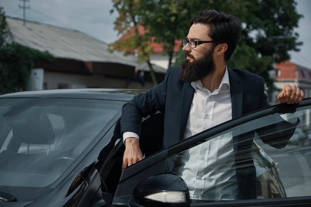 Homem confiante com roupa formal, segurando a mão na porta do carro aberta