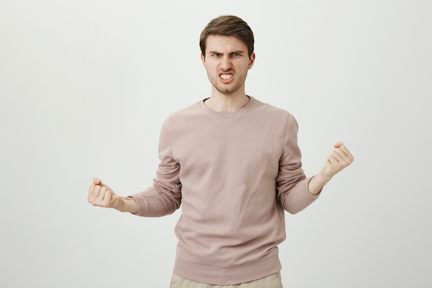 Homem confiante e determinado fazendo careta, punhos cerrados encorajando