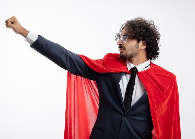 Homem confiante e jovem super-herói usando óculos ópticos, usando um terno com capa vermelha, levanta o punho e olha para o lado isolado na parede branca