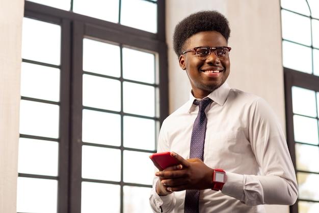 Homem confiante e positivo sorrindo em pé com seu telefone celular no escritório