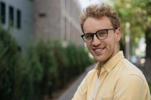 Homem confiante e sorridente usando óculos elegantes, olhando para a câmera em pé na rua