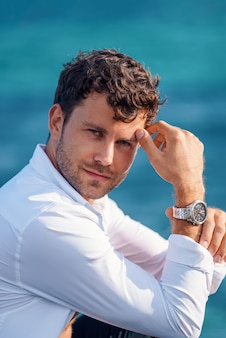 Homem confiante em camisa branca contra o mar