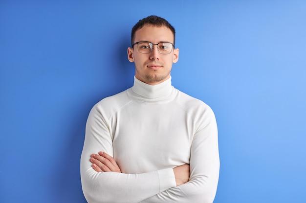 Homem confiante em óculos posando olhando para a câmera com os braços cruzados, vestindo uma camisa branca casual, isolado no fundo azul do estúdio