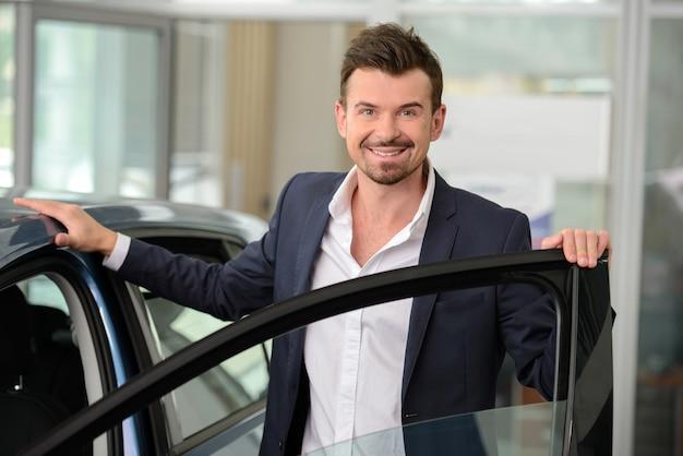 Homem confiante em trajes formais, inclinando-se para o carro.