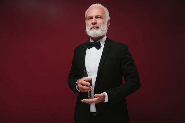 Homem confiante em um terno preto segurando uma taça de champanhe