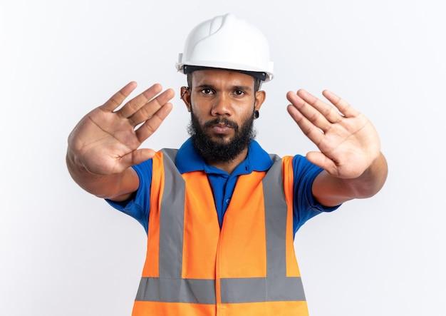 Homem confiante jovem construtor afro-americano de uniforme com capacete de segurança gesticulando a placa de pare isolado no fundo branco com espaço de cópia