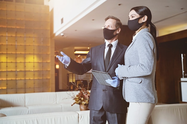Homem confiante mostrando um lindo saguão de hotel para sua jovem colega. máscaras em seus rostos