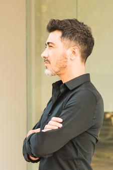 Homem confiante na camisa preta com os braços cruzados, olhando para longe