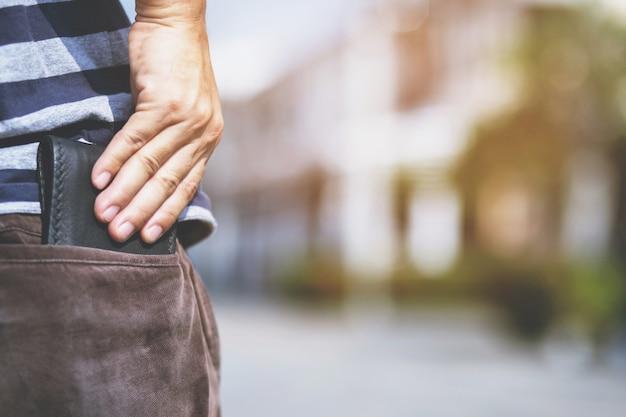 Homem confiante posando em segurança, mantendo sua carteira no bolso de trás da calça do bolso de trás. poupança de dinheiro para financiar.