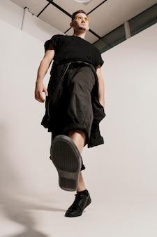 Homem confiante pulando caminhando contra branco