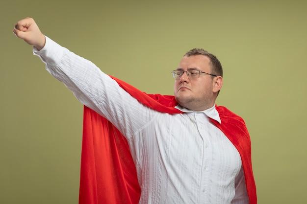 Homem confiante super-herói adulto com capa vermelha usando óculos com o punho esticado, olhando para o lado isolado na parede verde oliva