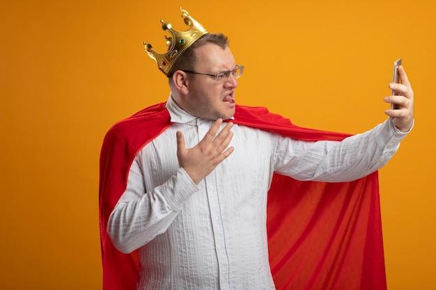 Homem confiante super-herói adulto com capa vermelha usando óculos e coroa, mantendo as mãos no ar, piscando e tomando selfie isolada na parede laranja