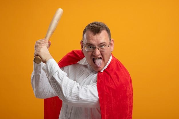 Homem confiante super-herói adulto com capa vermelha usando óculos, olhando para a frente, mostrando a língua segurando o taco de beisebol, preparando-se para bater isolado na parede laranja