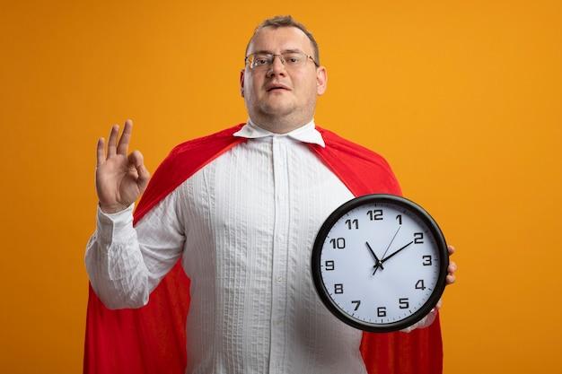 Homem confiante super-herói adulto com capa vermelha usando óculos, olhando para a frente, segurando o relógio, fazendo sinal de ok isolado na parede laranja
