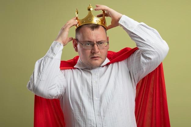 Homem confiante super-herói eslavo adulto com capa vermelha usando óculos e coroa olhando para o lado tocando a coroa isolada na parede verde oliva