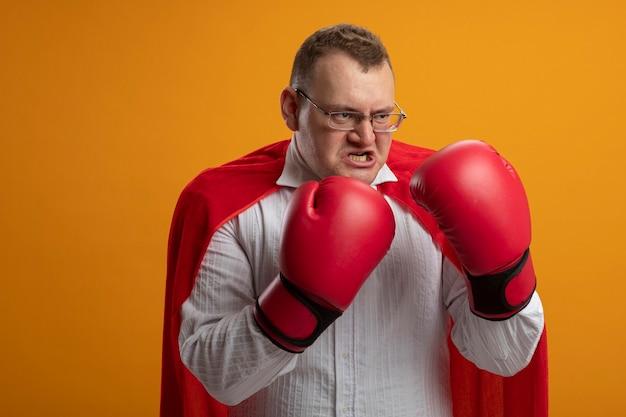 Homem confiante super-herói eslavo adulto com capa vermelha usando óculos e luvas box, olhando para o lado, fazendo gesto de boxe isolado na parede laranja com espaço de cópia