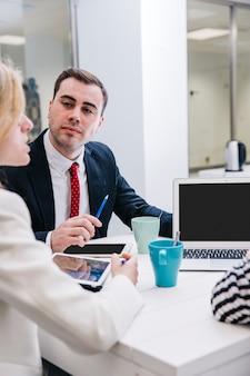 Homem confiante, tendo reunião com colegas de trabalho