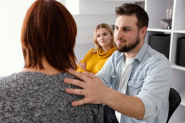 Homem confortando mulher em terapia Foto gratuita